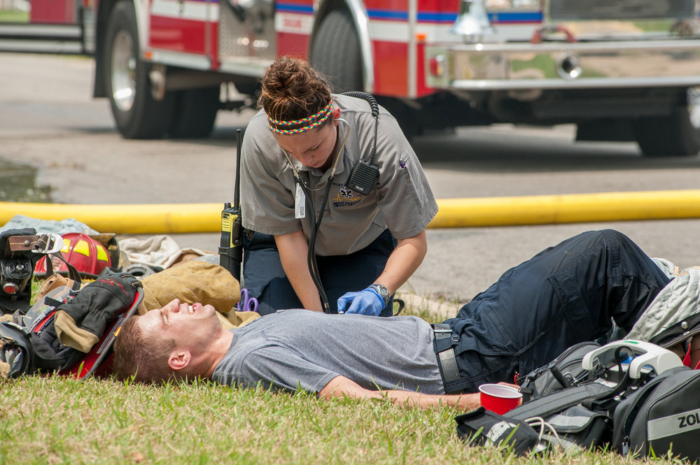 Riley County EMS paramedic Trisha Gross checks out her younger brother, Manhattan firefighter Austin Gross who was injured in a two alarm residential fire on Buttonwood Drive in Manhattan.