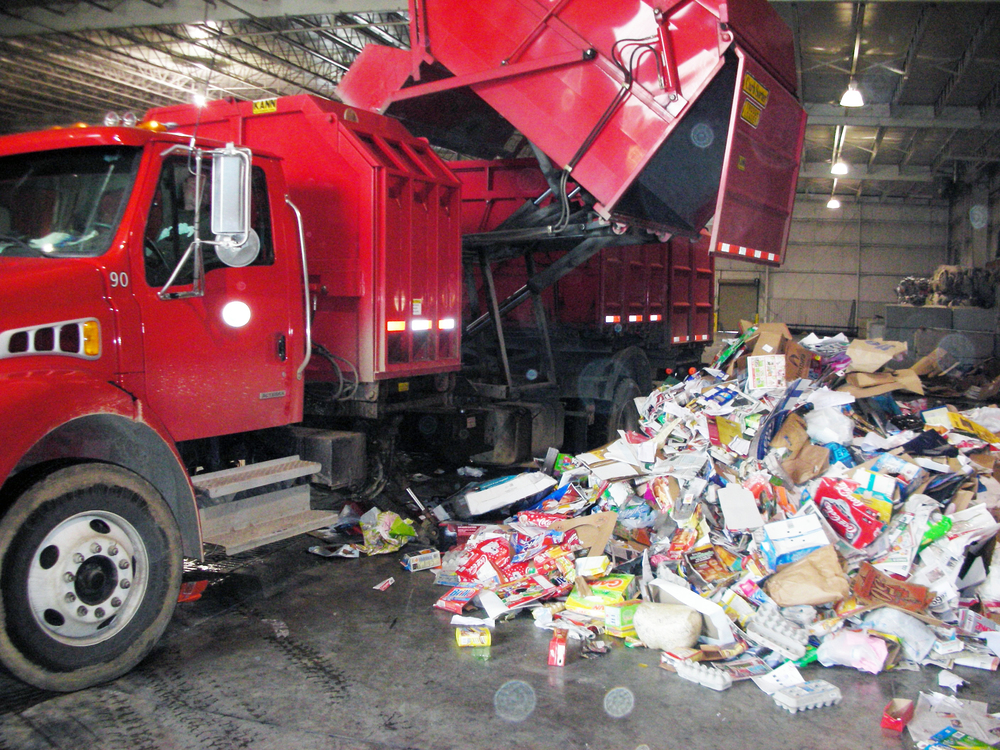 A red City of Dalton Curbside Recycling truck drops off mixed paper for recycling at the MRF.