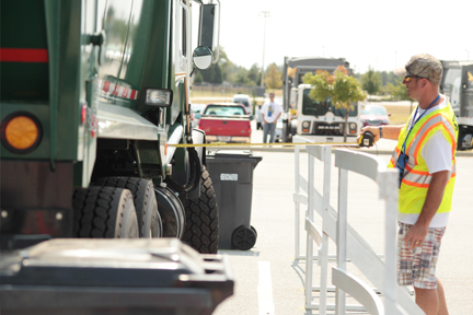 A Road-E-O judge measures the distance between the Front Loader and the rail to determine the accuracy of driver Chad Shook during the competition.