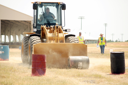 Marlon Cole guides a barrel through part of the obstacle course for the Rubber Tired Loader as Road-E-O judges look on.
