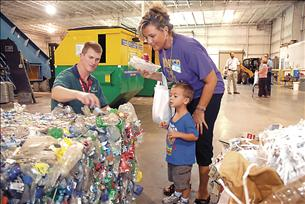 Staff Photo by Tim Barber:    Michael Foxx, right, Recycling Center operations manager at the Dalton-Whitfield Regional Solid Waste Management Authority, punctures a plastic bottle as Matthew Ryerson, 3, and North Whitfield Middle School teacher Jill Ryerson listen for air to be released at recent open house.
