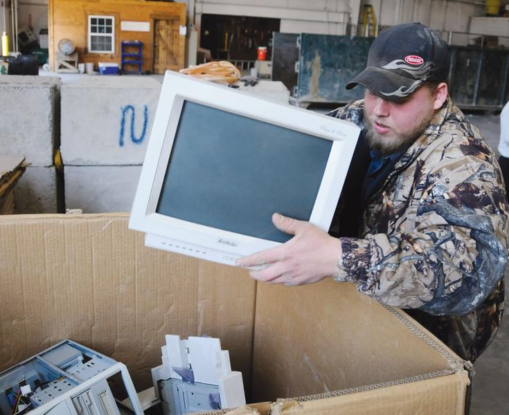 Staff member at the recycling center loads a monitor into a gaylord box for electronic waste recycling collection.