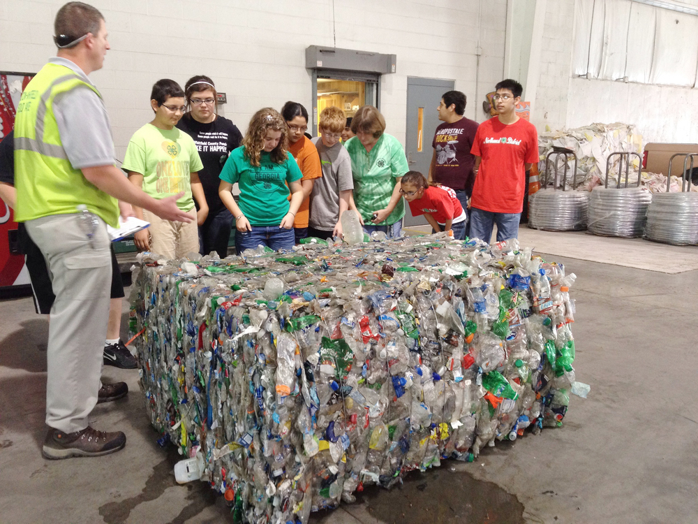 Students guess how many plastic bottles are in a bale during a tour.