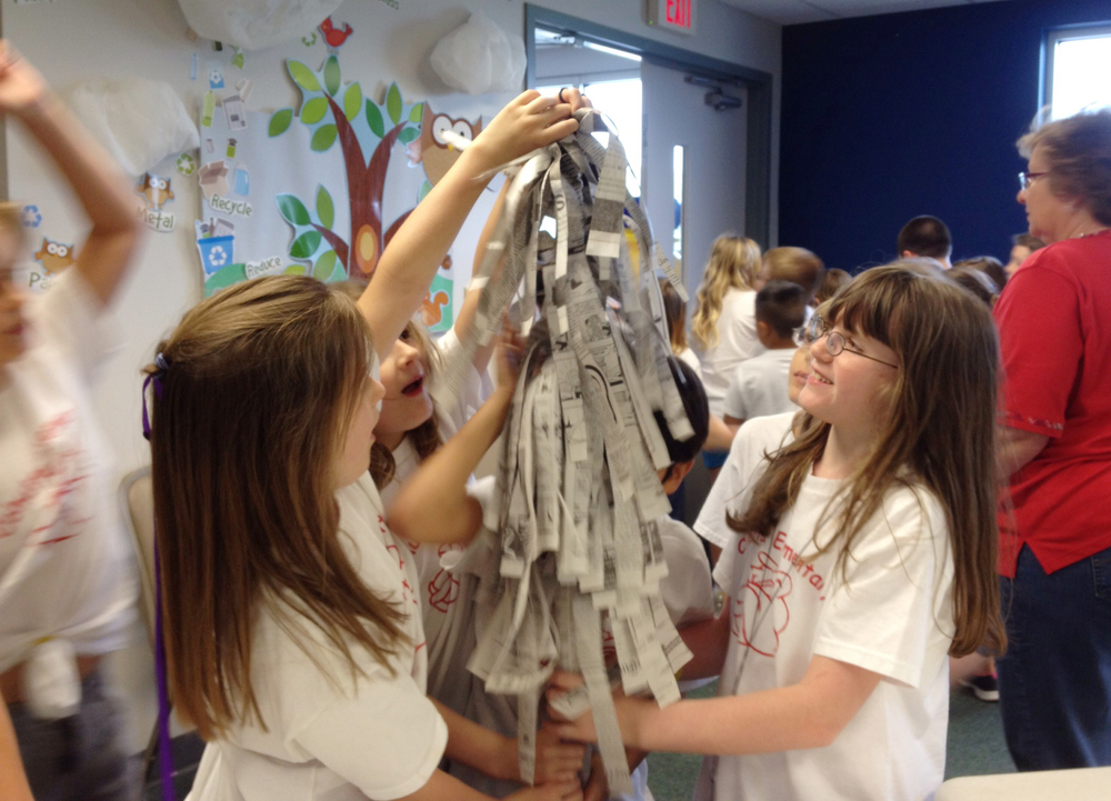 Students on a tour make a tree grow out of newspaper during an activity in the education room.