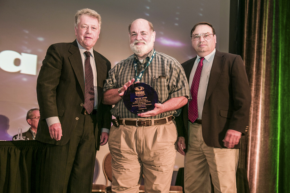 Harvey Levitt (center) receives the Professional Achievement Award for the Public Sector at a recent conference from representatives from the Solid Waste Association of North America.