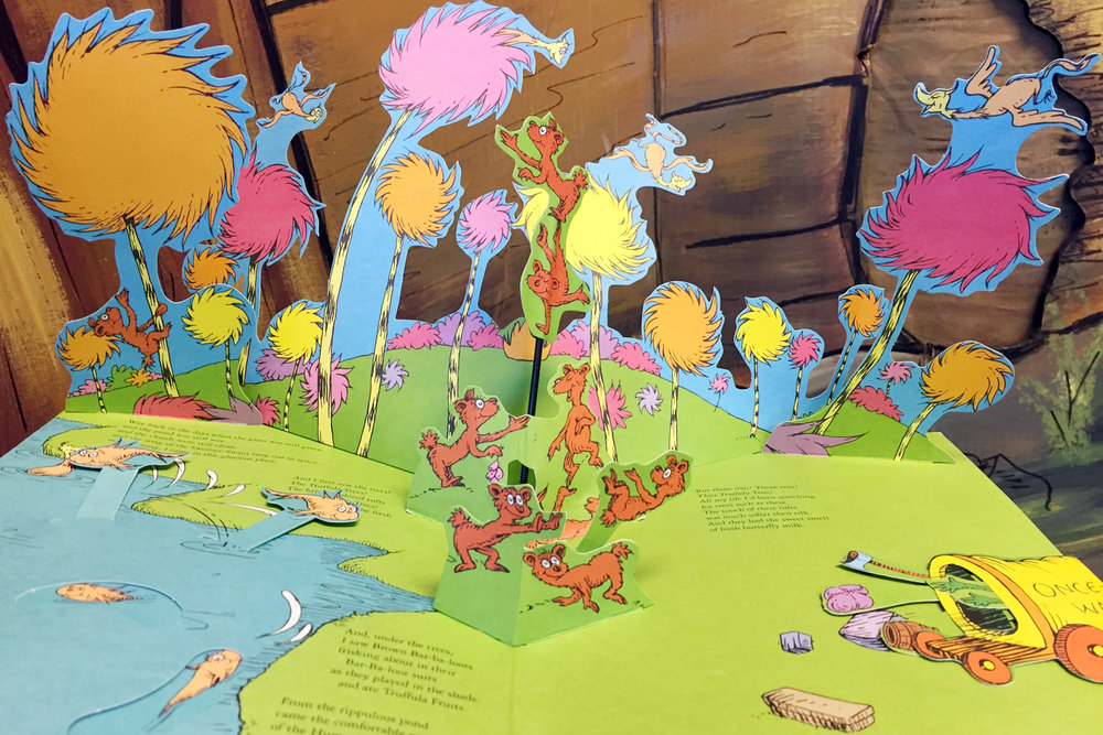 Colorful truffula trees and happy creatures are illustrated in the pop-up book version of The Lorax by Dr. Seuss. Celebrate Read Across America Day and Dr. Seuss' birthday by reading this and other eco-friendly books with your child.