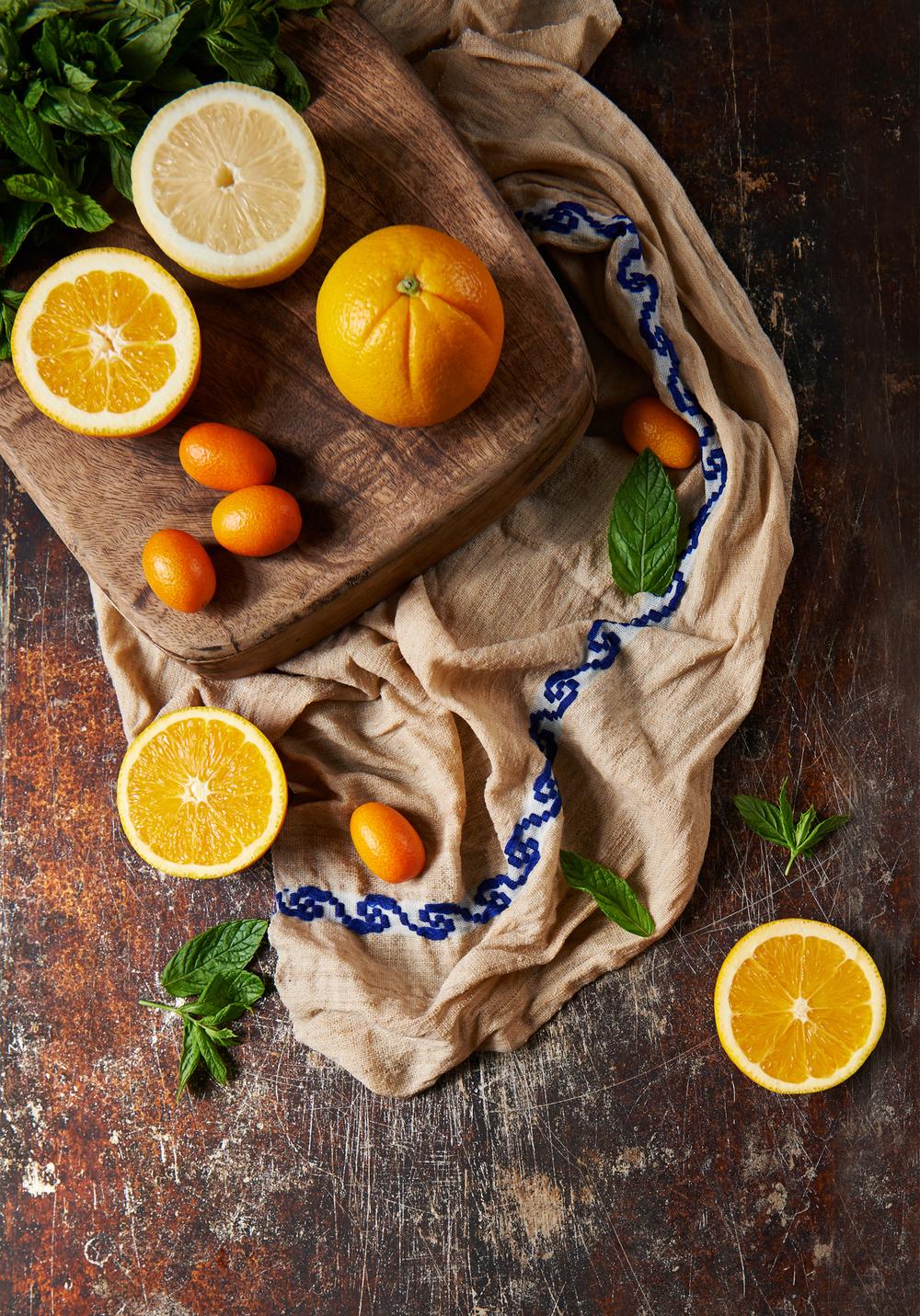 still life image of oranges and kumquats