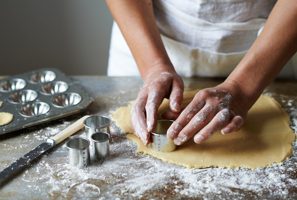 lifestyle image of woman cutting biscuits from pastry