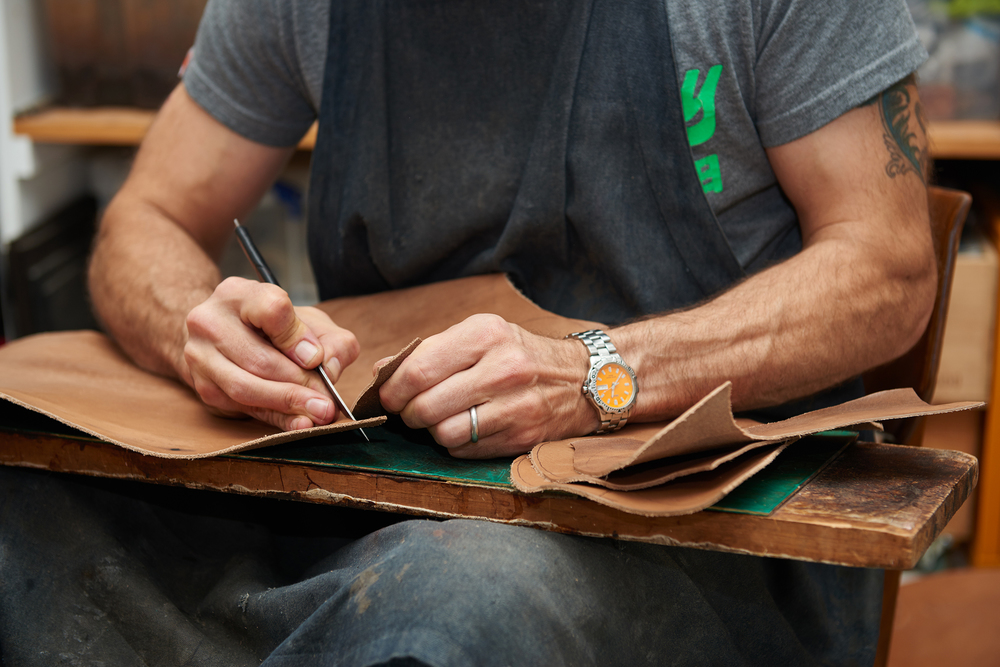 shoemaker cutting leather by hand