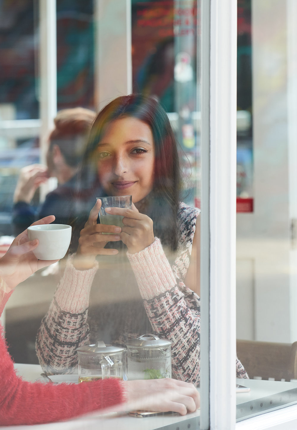 photograph of a girl  in a cafe window