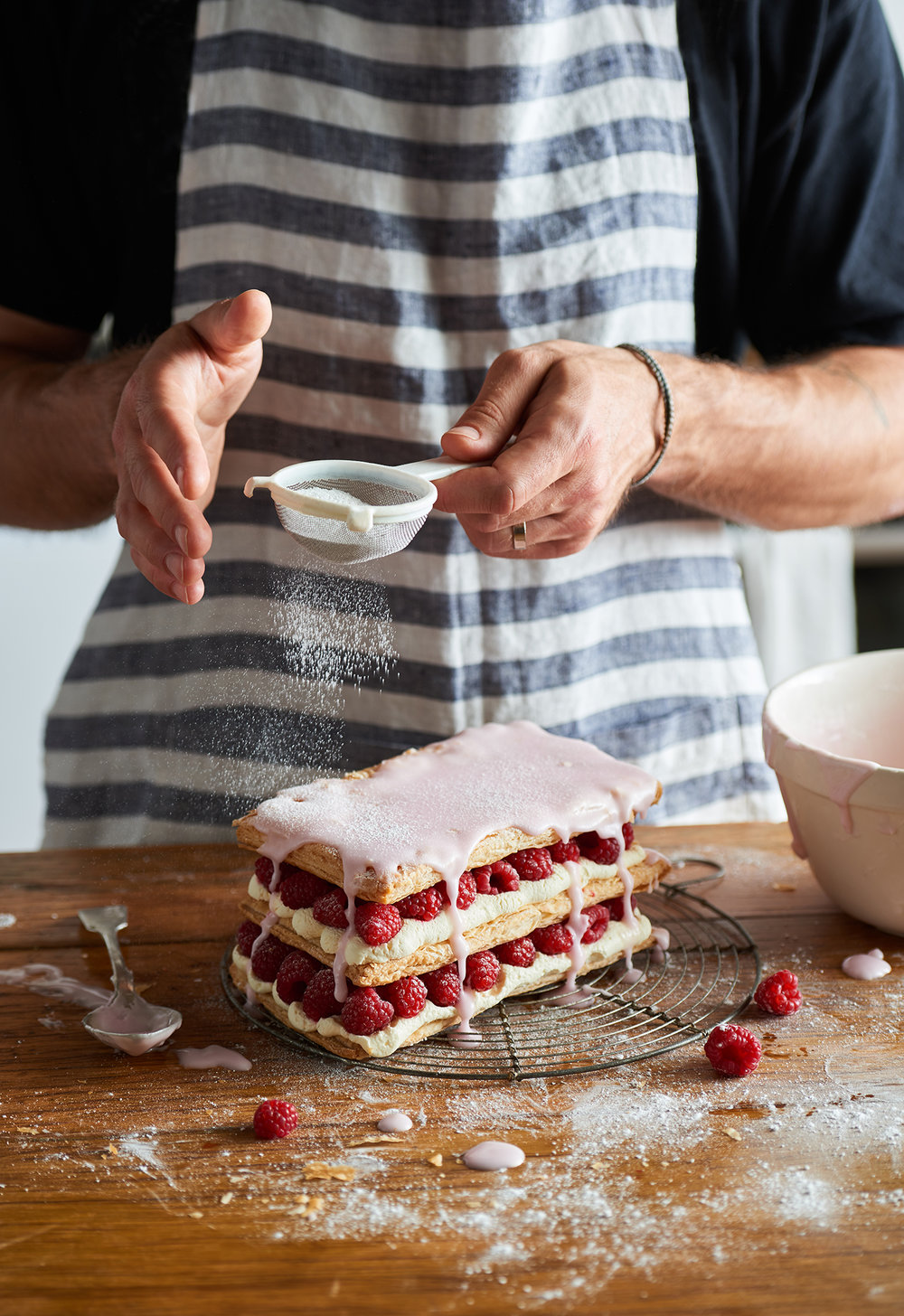 man decorating a raspberry and cream cake