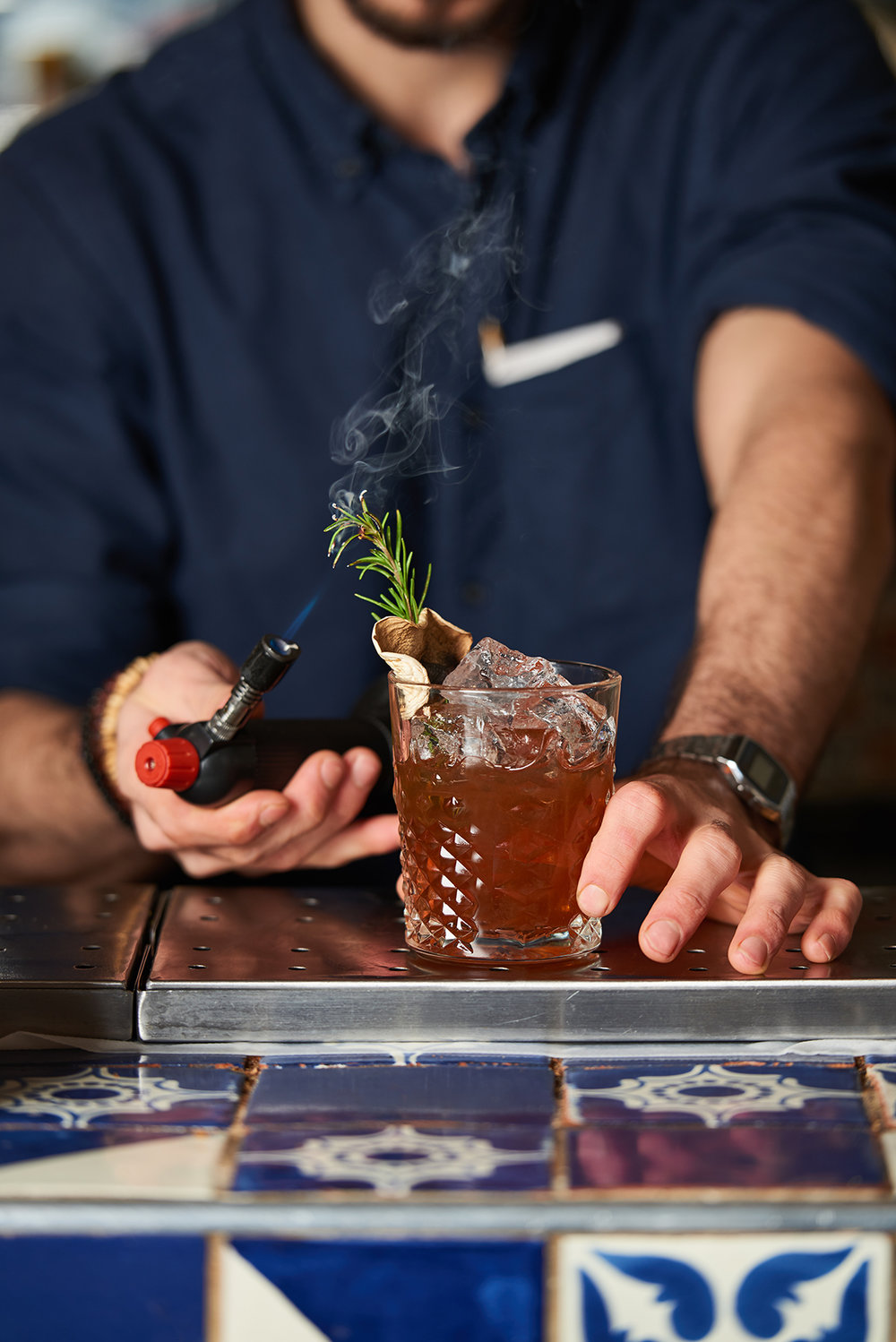 bartender with a rosemary cocktail