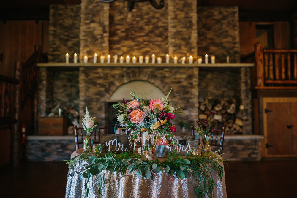 Flowers by Lace and Lilies - colorful head table, bridal bouquet, bride, mr & mrs, garden rose, orange, coral, red, foliage, garland, head table, sweetheart table, candles, summer wedding, colorado, spruce mountain ranch
