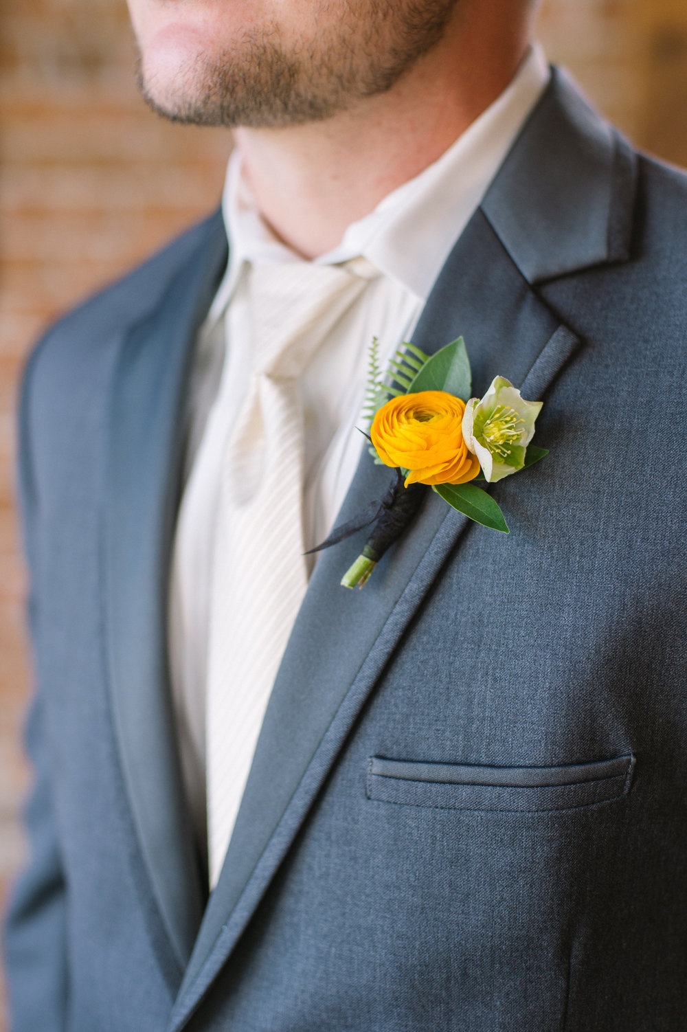 Flowers by Lace and Lilies, Yellow Ranunculus, Fern and Hellebores boutonniere, industrial wedding, blue suit groom