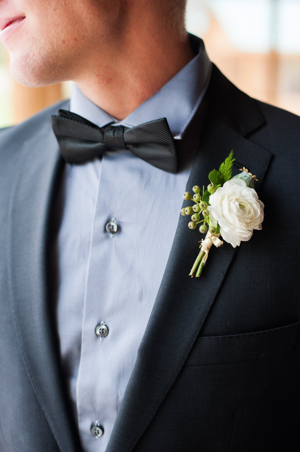 Flowers by Lace and Lilies, formal black tie wedding, ranunculus, poppy pod and fern boutonniere. Bow tie.