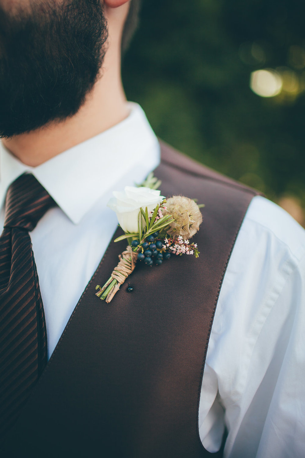 Flowers by Lace and Lilies, white spray rose, blue privet berry and scabiosa pod boutonniere, grooms brown wedding vest
