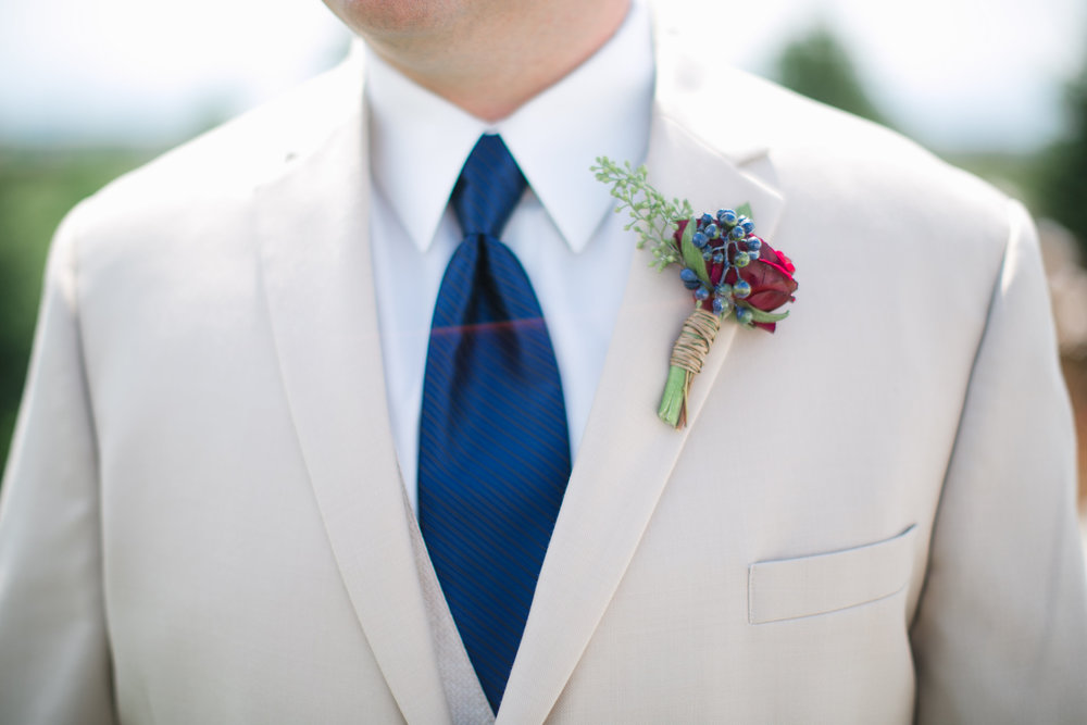 Flowers by Lace and Lilies, red ranunculus and blue berry boutonniere - navy burgundy and green