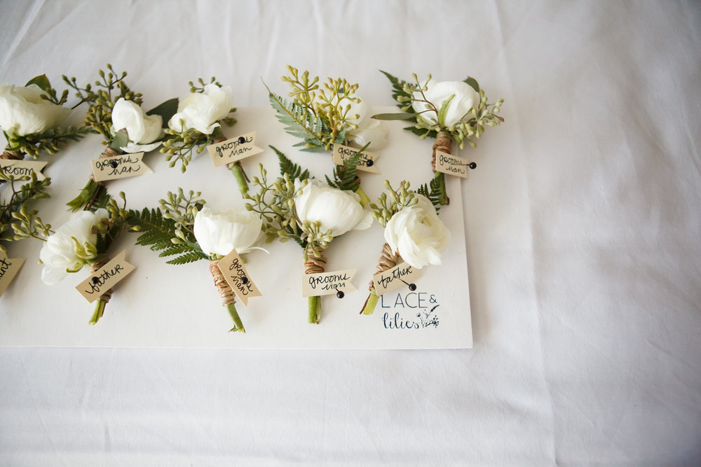 Flowers by Lace and Lilies, boutonniere board, white ranunculus and seeded eucalyptus with twine wrap