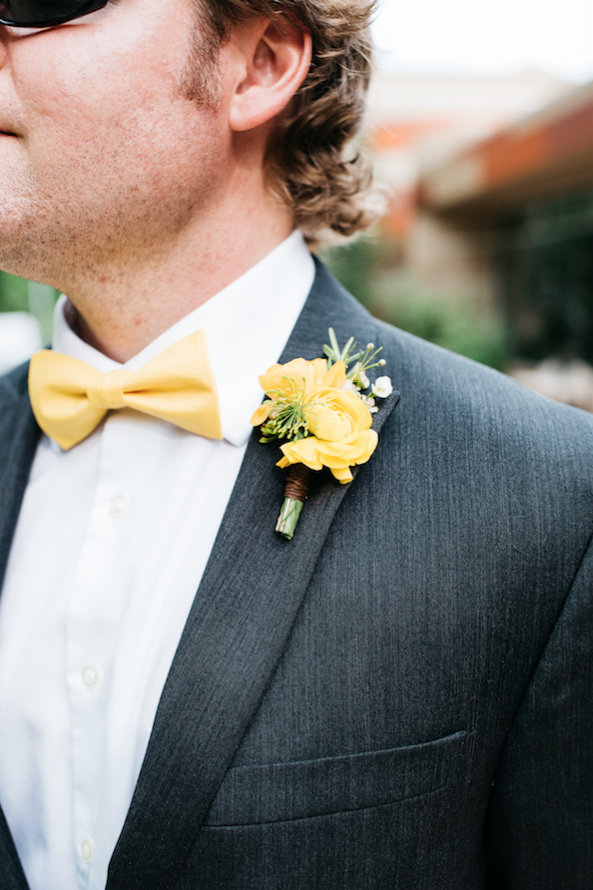 Flowers by Lace and Lilies, yellow ranunculus and herb boutonniere, bow tie and grey suit groom