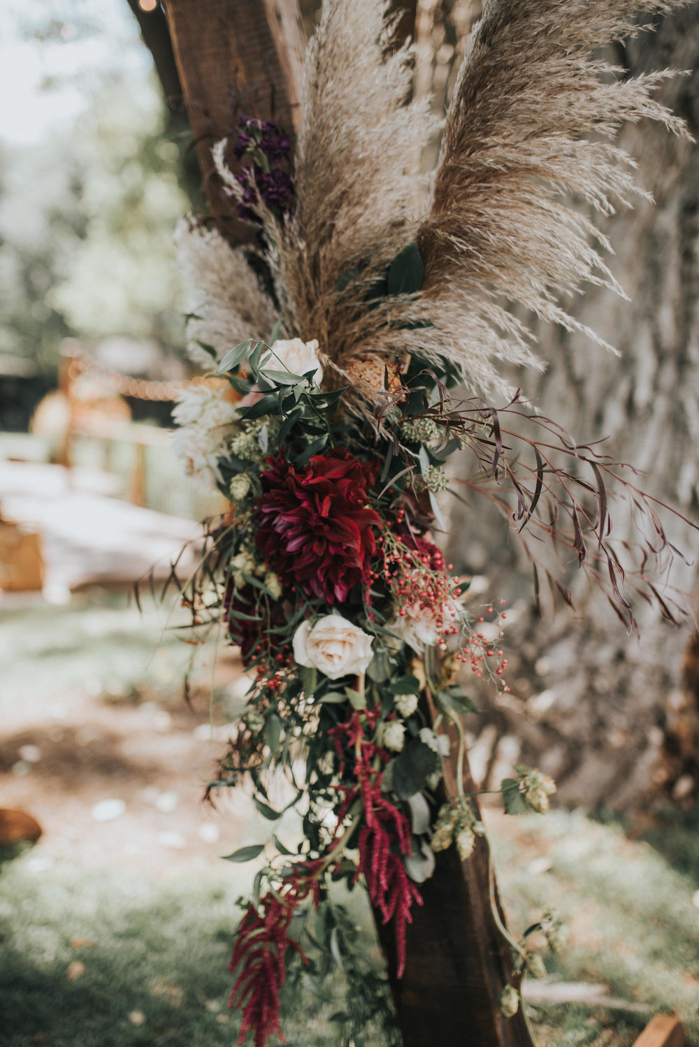 Flowers by Lace and Lilies, wedding flowers, jewel tones, pampas grass, hops, texture, colorado wedding, a-frame arch, arch flowers, altar flowers, ceremony flowers, moody toned wedding, pampas grass