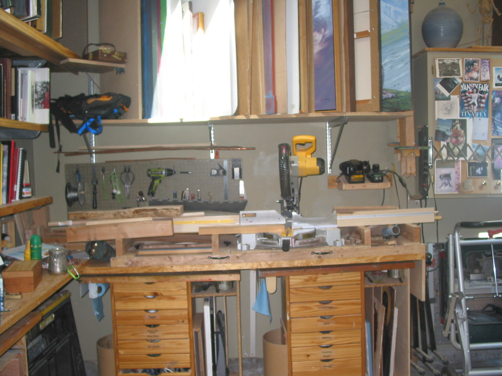 Pictured here is my Chop Saw and table. The drawers you see underneath are rolling easels that my painting students use and the mast are hanging on the wall in the upper right. You can see painting storage above it and my art book collection on the left.
