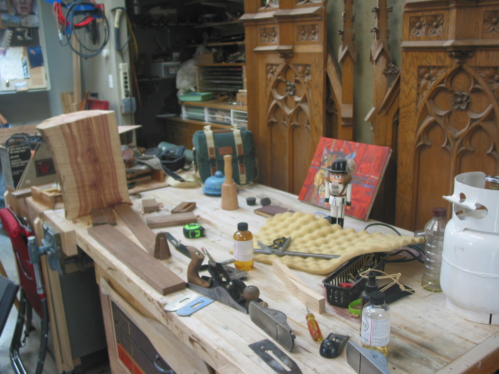Here is the work bench I made and there is half a log of Juniper. I may make a stool out of. I loved the grain and the colors., Some hand planes and a guitar neck I am making.