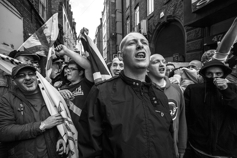 Members of the Far-Right group EDL hurl abuse at riot police after being kettled-in on a back street in Manchester