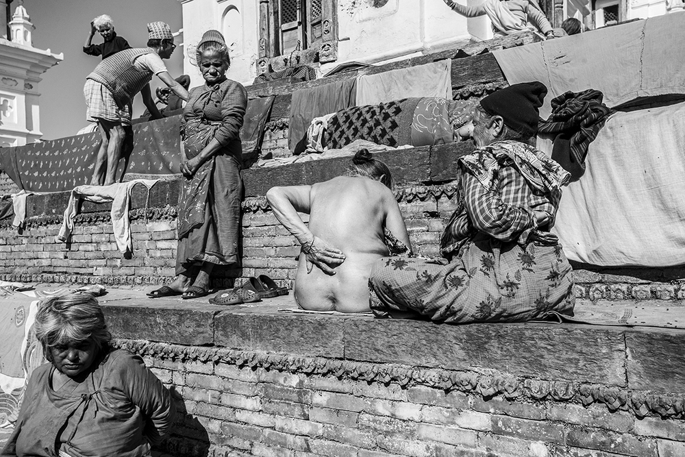 Female resident with severe back pain sits, half naked in the main courtyard of the home waiting for a fellow resident to give her a back massage.
