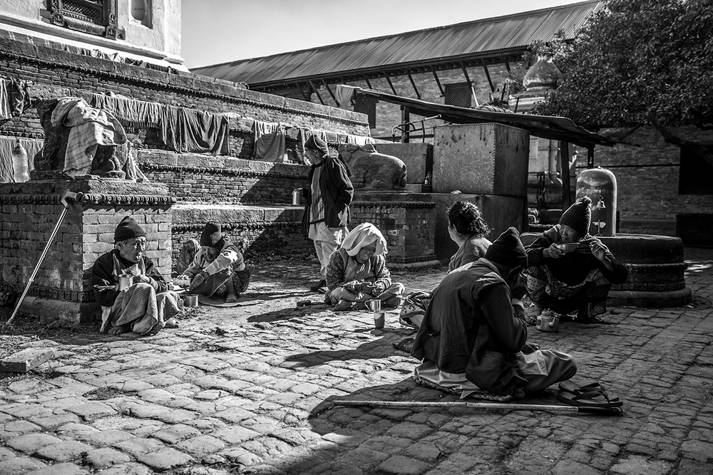 Residents of Pashupati Briddhashram Social Welfare Home for the Elderly sit in the central courtyard of the home.