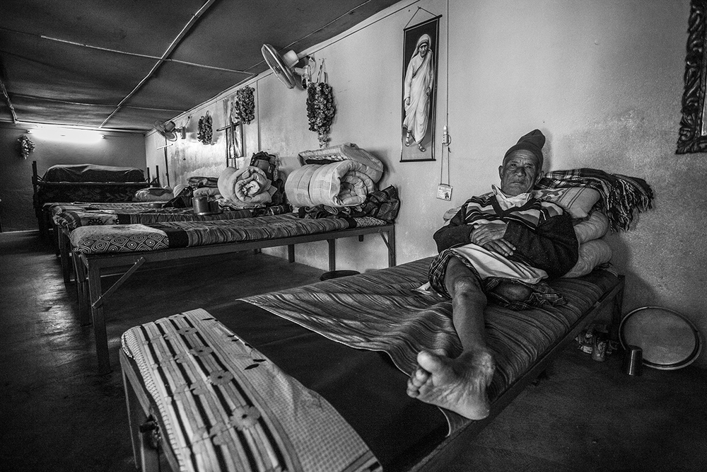 Male resident and amputee lays in bed in a communal sleeping area under a picture of Mother Teresa.