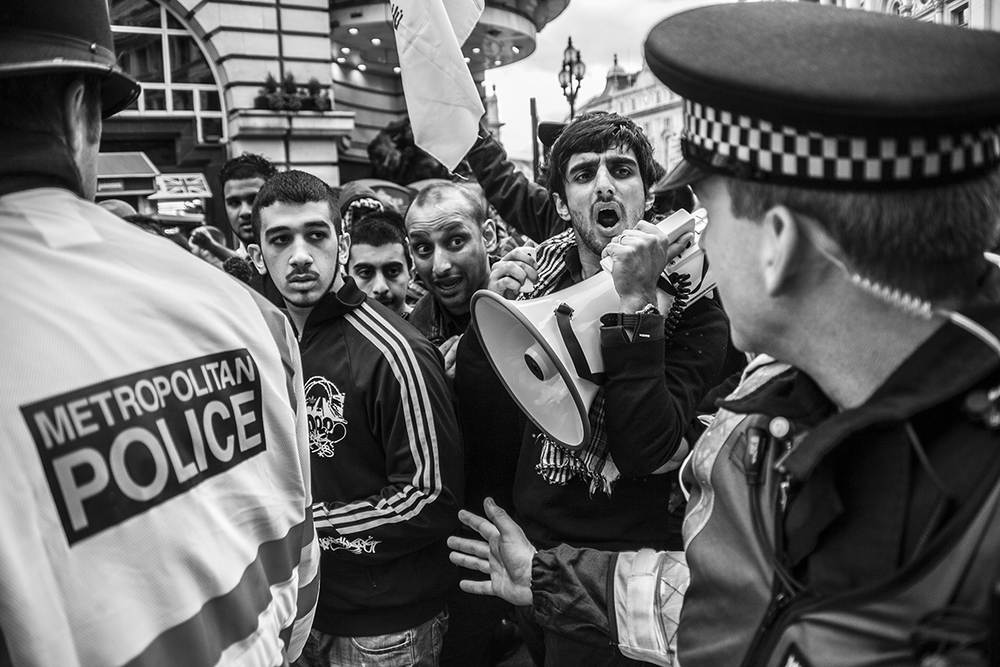 Asian youths marching at an Al Quds rally in London are held back by police as they pass English Defence League members staging a counter-demonstration in Picadilly Circus, London. 13/09/2009