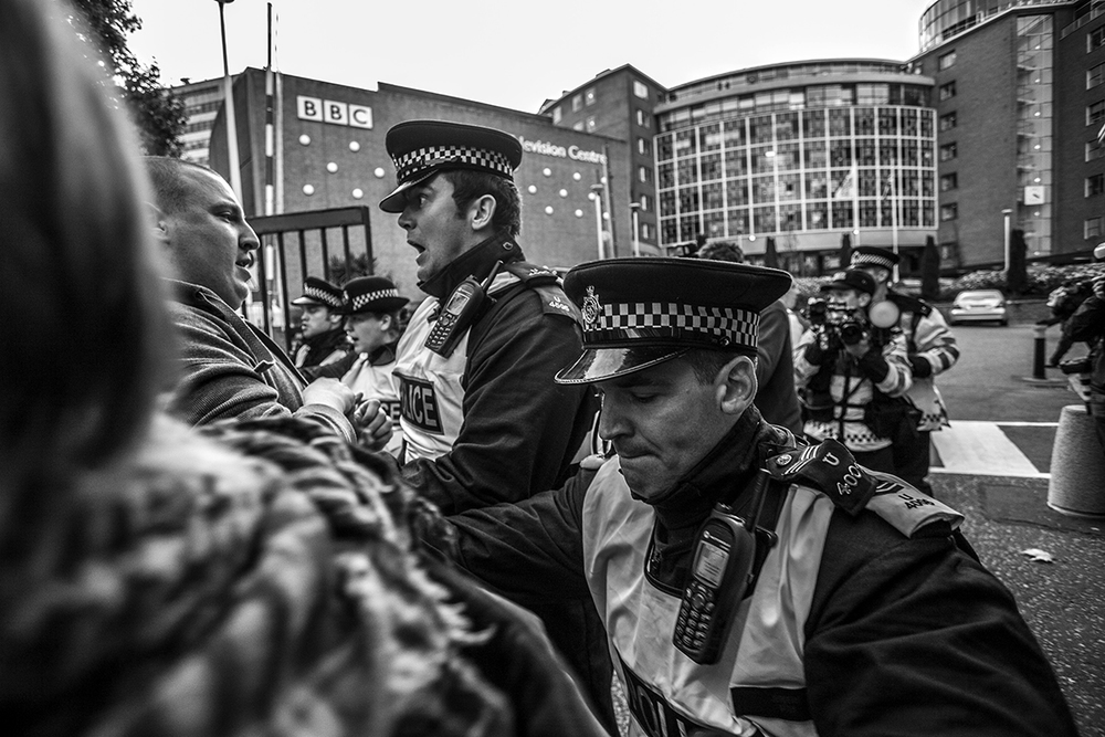 Police attempt to hold back UAF supporters as they storm the front gates of BBC television centre during a  protest against the appearance of BNP leader Nick Griffin on 'Questiontime'