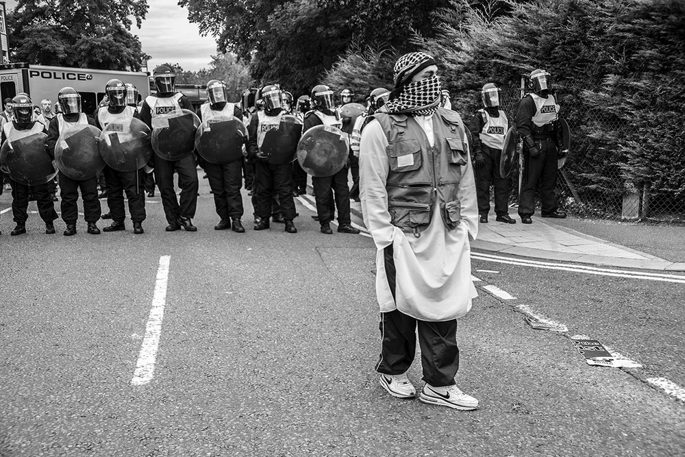 An Asian youth wearing flak jacket with his face obscured stands in front of police lines during a tense stand off between local Muslims, UAF and Casuals United/ SIOE (Stop Islamisation of Europe) protesters. Harrow, London. 11/09/2009