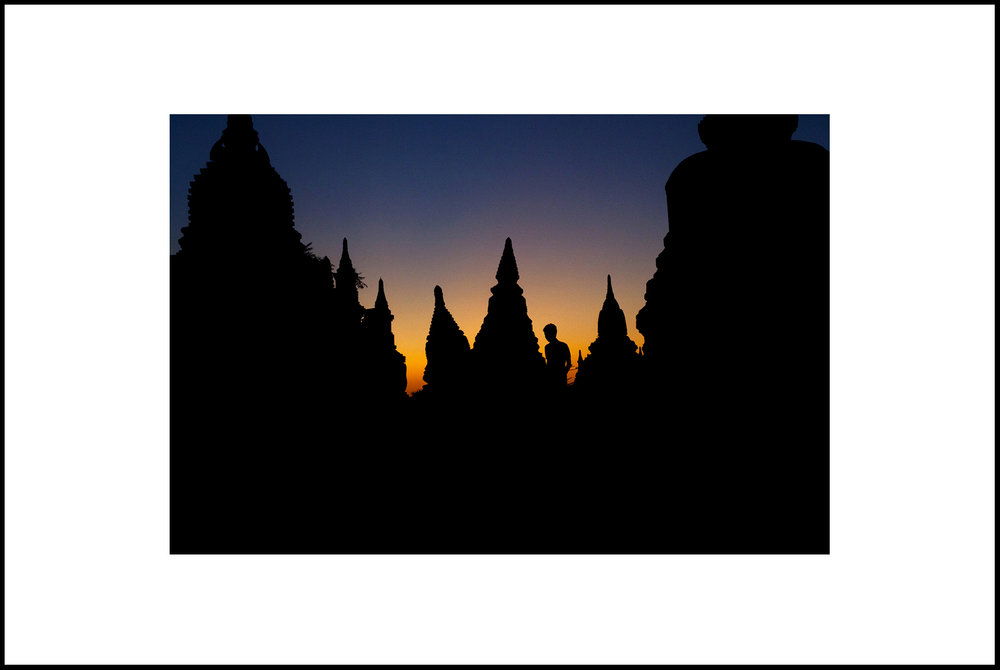Man Walks Among Stupas In Bagan at sunset. Myanmar. 2014.