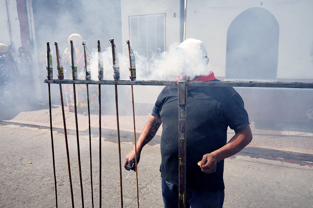 Man lights fireworks ahead of a procession for San Antonio Abad, During Fiesta De Enero in Chiapa De Corzo, Chiapas, Mexico.