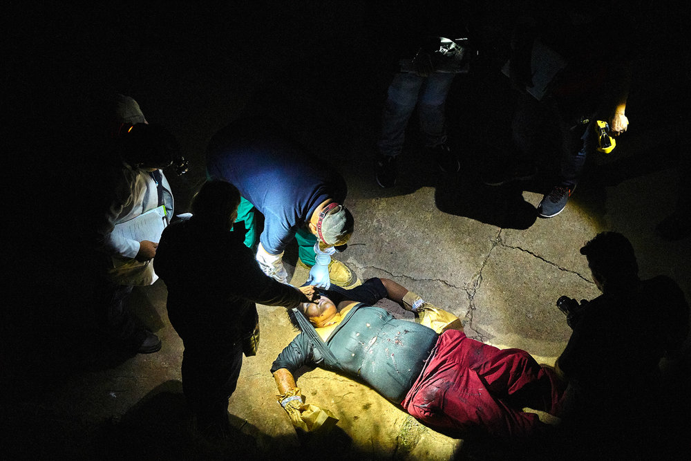 forensic team investigates the scene of a murder in Olocuilta. Four gang members approached a female candy vendor on a secluded pathway in Montelimar neighbourhood and shot her over 20 times after she refused to hand over her earnings.