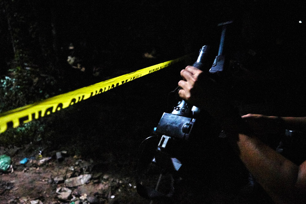 Kalo prepares to shoot footage at a police cordon in Mejicanos.  An elderly woman was shot dead whilst sleeping in a hammock outside her home. During the same evening 16 intentional homicides were recorded across El Salvador with at least 11 being committed in or around the capital