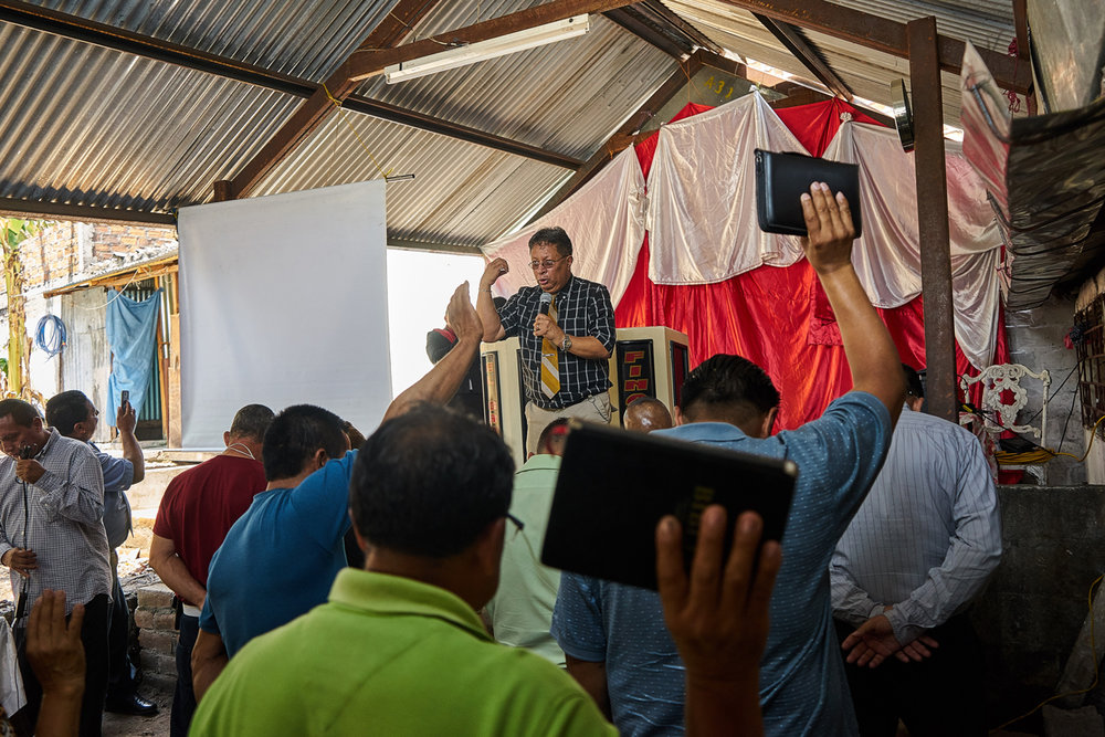 Pastor Saul conducts a sermon during a Culto for Ex addicts and gang members in Mejicanos.