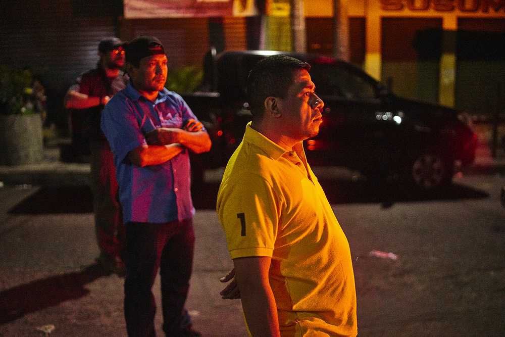 Onlookers at the scene of a shooting homicide in downtown San Salvador. A security guard was shot in a late night restaurant. his gun was stolen in the incident.
