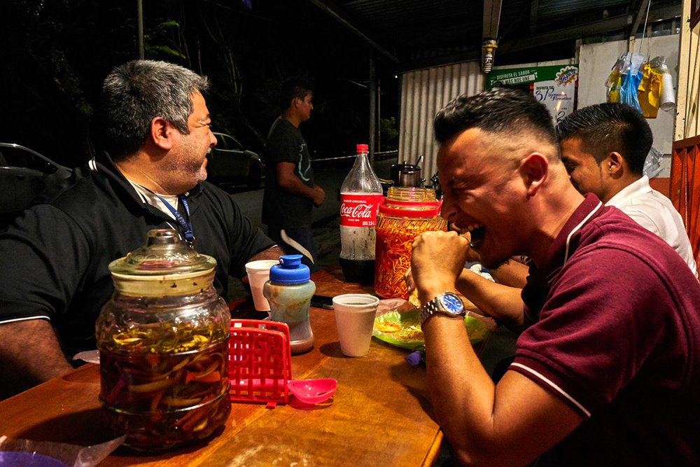 Francisco (left) a night shift photographer for popular national tabloid newspaper La Prensa Grafica, enjoys pupusas with colleagues during a short break on a busy Saturday night in San Salvador.
