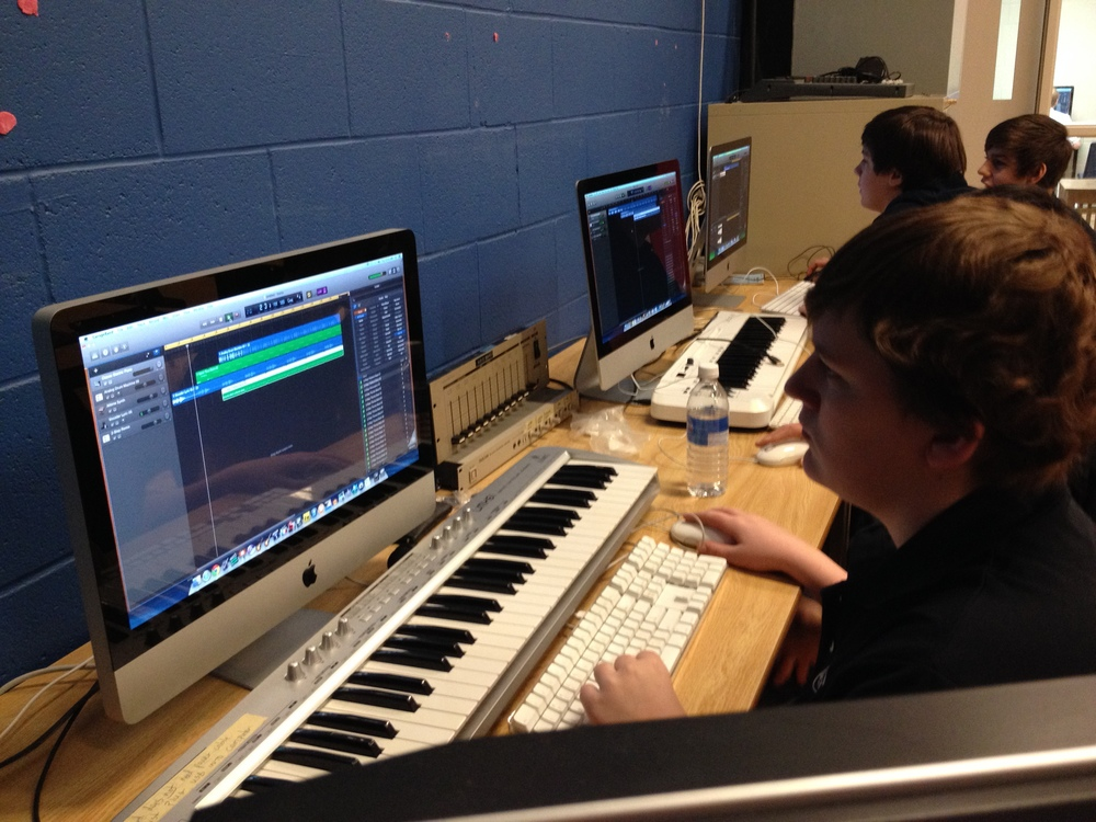 Students using Garageband to create their songs.