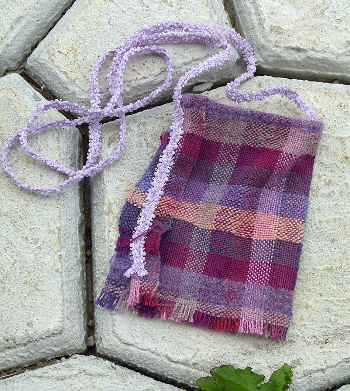 "This sweet purple purse is going to my seamstress friend Evelyn who helped me create a pattern from my favorite shirt and got me started on sewing my beautiful cloth. This purse is unlined and is about 5""x7"". I braided three pieces of decorative ribbon to make a soft but strong strap which also runs down the side seam on the outside."