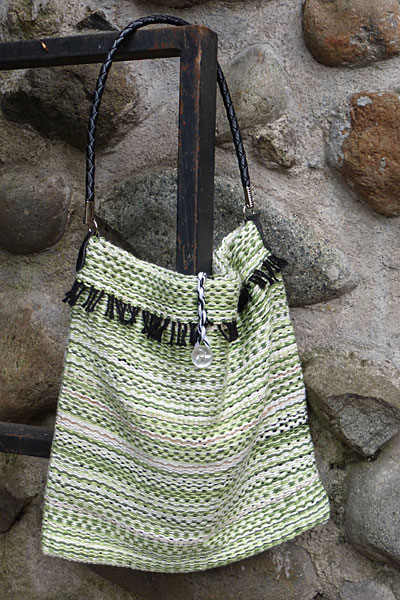 I love the greens in this bag and the commercial leather strap works well with the black fringe warp. This bag is lined with white cotton and has one pocket inside. The closure is a twisted black and white cord with a white pearly button.