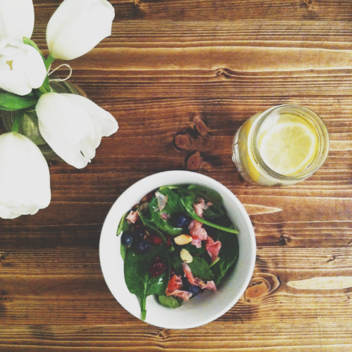 spring salad: spinach leaves topped with blueberries, almonds, ham and raspberry vinaigrette.
