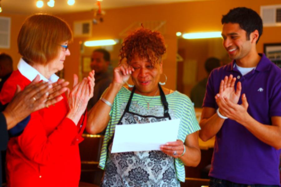 LEND's first loan client Gigi Giles (middle) receives her loan completion certificate from Evanston Mayor Elizabeth Tisdahl (left) and former LEND President Gaurav Kikani (right).