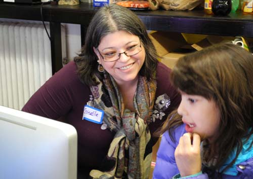 Giselle helps a young girl sign up for a free art program at a recent ElevArte Open House.