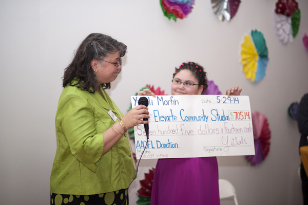 Yitlali Morfin presents ElevArte's Executive Director, Giselle Mercier with a check for $705.14. Yitlali raised the funds by visiting local businesses and telling them about the impact that ElevArte has had on her.