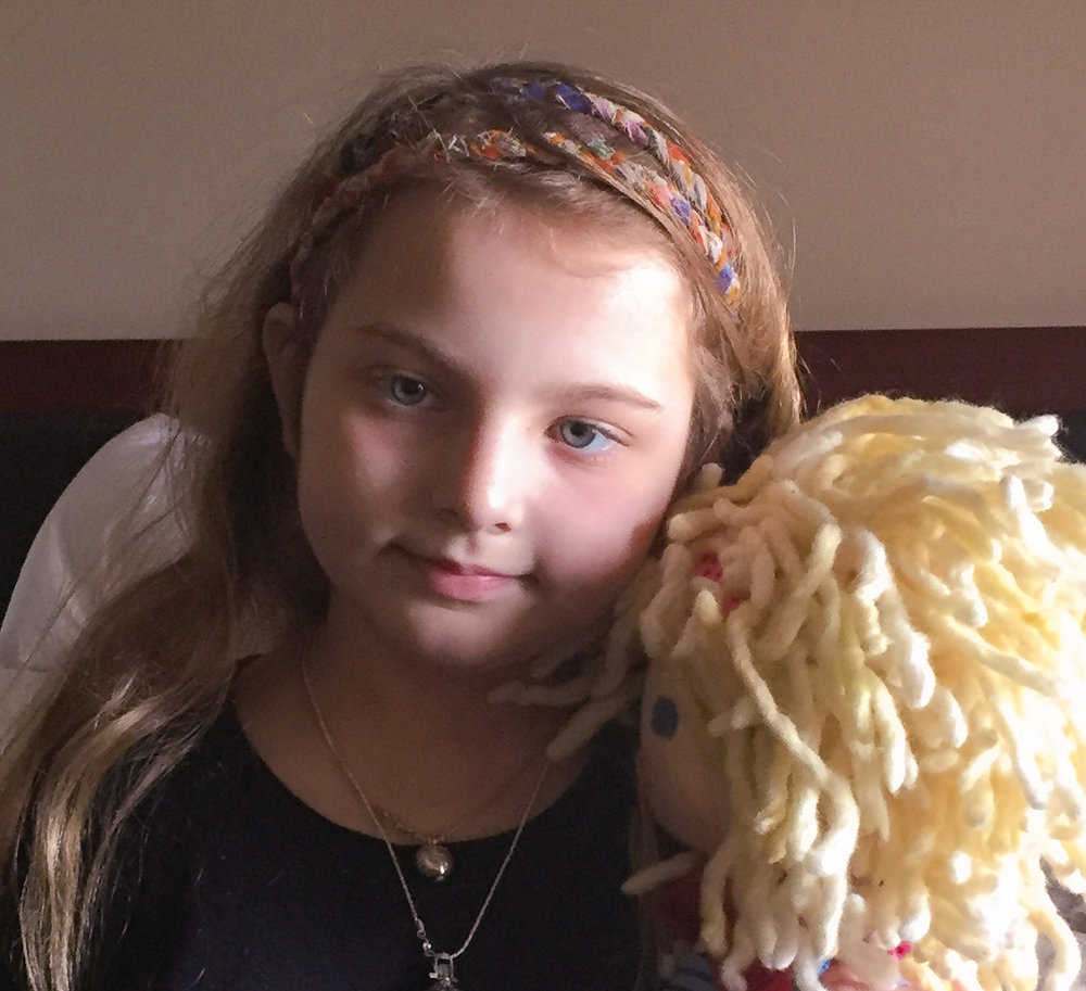 "Zamora Moon and her doll named ""Forget"" because she wanted to forget cancer, 2016"