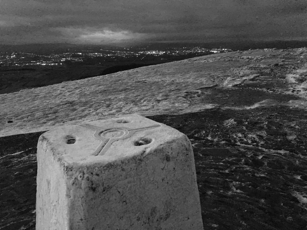 Pendle Hill trig point looking towards the lights of Burnley.