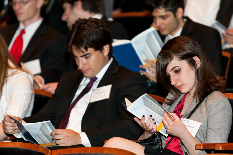 Engineering students reading the award ceremony's program.